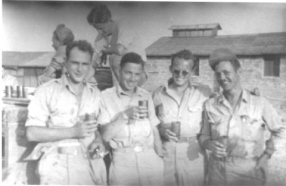 Celebrating 2 years overseas. Maurice Weiner, Phil Goldstein, Edgar Combs, Bauer. (After the war, Goldstein changed his name to Graham)