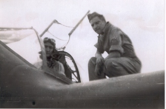 Harold T. Harper being strapped into his cockpit by his Crew Chief, Michael Whiteford.