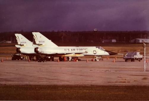 The F-106s on alert. Griffiss AFB, 8 November 1985. These alert birds are parked outside while maintenance is being performed on the Alert hangars. Note that there are no pitot or inlet covers , and the power carts are hooked up and out of the way. Note, too, the Missile Caskets on the trailer to the right. In the background, the Griffiss AFB Weapons Storage Area can be seen with its guard tower and concertina wire topped fences. The Weapons Storage Area is across the ramp in the picture.